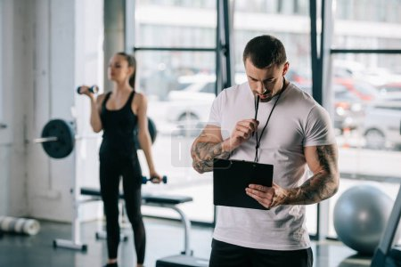 male personal trainer with clipboard and young sportswoman exercising with dumbbells behind at gym