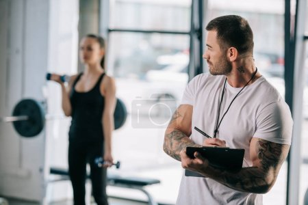 male personal trainer writing in clipboard and young athletic woman exercising with dumbbells behind at gym