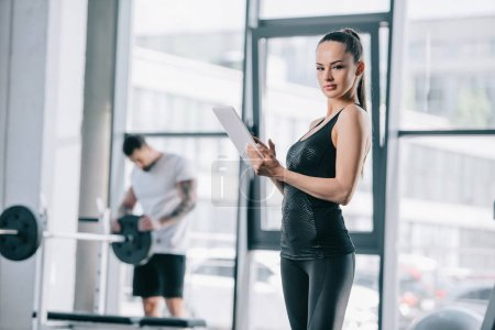 young female trainer with digital tablet and athletic man with barbell at gym