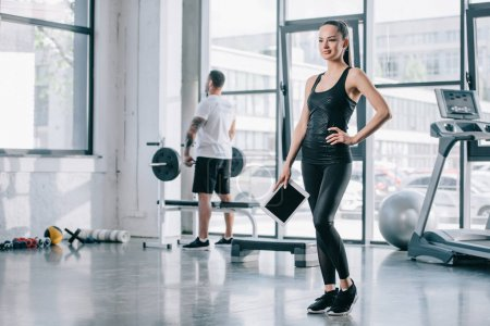 young female personal trainer with digital tablet and athletic man with barbell behind at gym