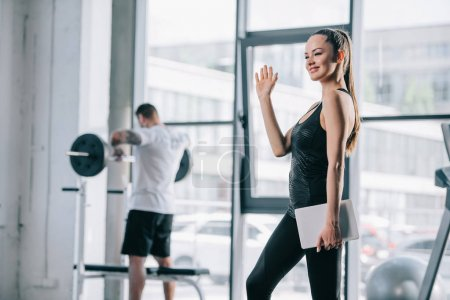 female personal trainer with digital tablet waving hand and athletic man exercising with barbell behind at gym