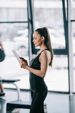 side view of female personal trainer with digital tablet at gym