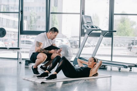 male personal trainer with timer and athletic woman doing abs on fitness mat at gym