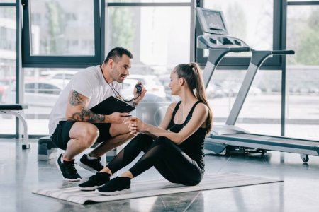 male personal trainer showing timer to young athletic woman on fitness mat at gym