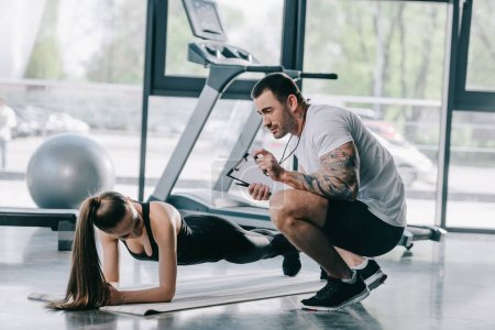 male personal trainer showing timer to young athletic woman doing plank on fitness mat at gym
