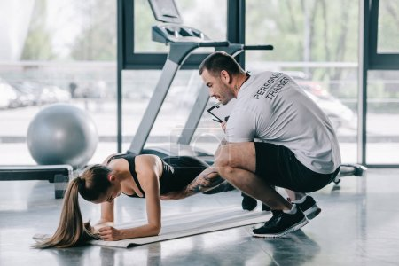 male personal trainer helping young athletic woman to doing plank on fitness mat at gym