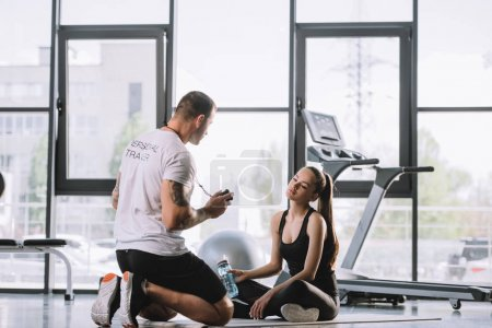 male personal trainer showing timer to young athletic woman sitting on fitness mat with bottle of water at gym