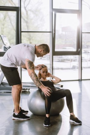 male personal trainer with timer and young athletic woman doing abs on fitness ball at gym