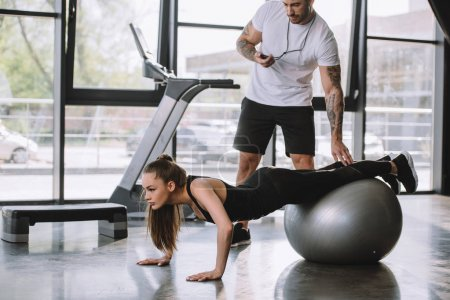 male personal trainer with timer and young athletic woman doing push ups on fitness ball at gym