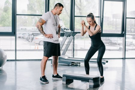 young athletic woman doing step aerobics exercise and male personal trainer at gym