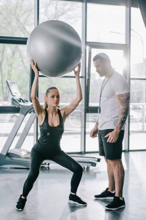 male personal trainer looking at sportswoman exercising with fitness ball at gym