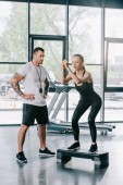 male personal trainer and young sportswoman doing step aerobics exercise at gym