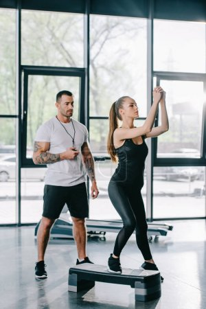 young sportswoman doing step aerobics exercise and male personal trainer with timer in hand at gym