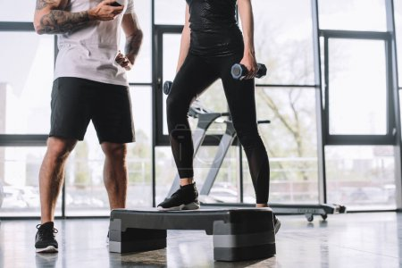 cropped shot of male personal trainer with timer and young sportswoman doing step aerobics exercise with dumbbells at gym