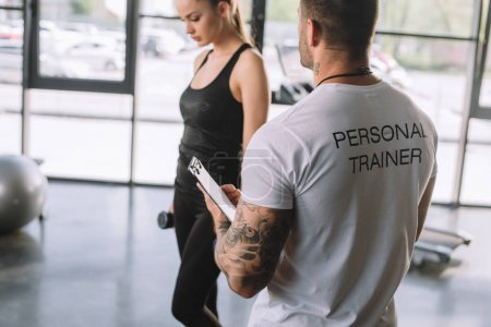 Photo for Rear view of male personal trainer with clipboard and young sportswoman with dumbbells at gym - Royalty Free Image
