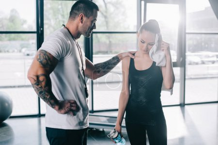 male personal trainer cheering up young sportswoman with bottle of water wiping face with towel at gym