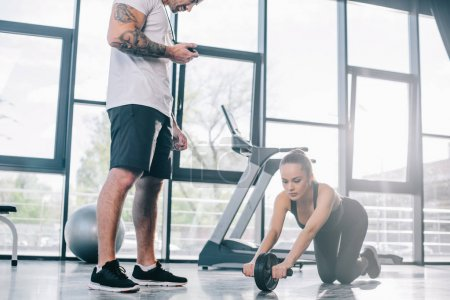 male personal trainer with timer and young sportswoman doing exercise with abs roller at gym