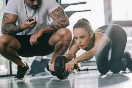 male personal trainer sitting with timer and young sportswoman doing exercise with abs roller at gym