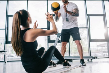 male personal trainer and sportswoman doing exercises with ball at gym