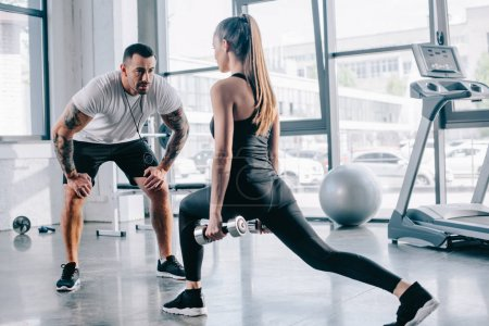 male personal trainer looking at sportswoman doing sit ups with dumbbells at gym