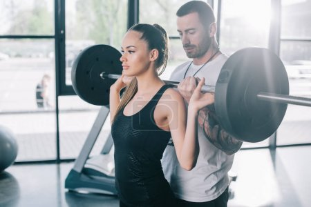 male personal trainer helping sportswoman to do exercises with barbell at gym