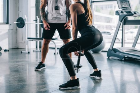 sportswoman doing exercises with dumbbell and male personal trainer standing near at gym