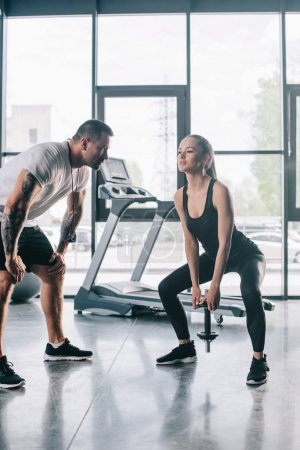 male personal trainer looking at sportswoman doing exercises with dumbbell at gym