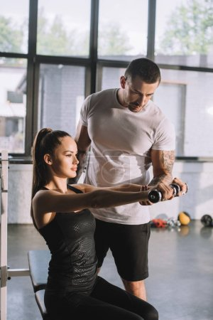 male personal trainer helping sportswoman to do exercises with dumbbell at gym