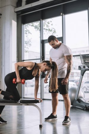 male personal trainer looking at sportswoman exercising with dumbbell at gym