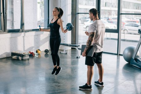 male personal trainer looking at sportswoman exercising with jump rope at gym