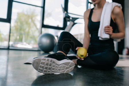 Photo for Cropped shot of sportswoman resting with towel and apple on gym floor - Royalty Free Image
