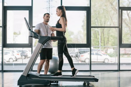 male personal trainer looking at sportswoman on treadmill at gym