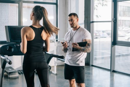 male personal trainer using timer while sportswoman running on treadmill at gym
