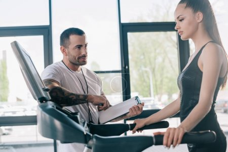 male personal trainer holding clipboard and sportswoman looking at treadmill screen