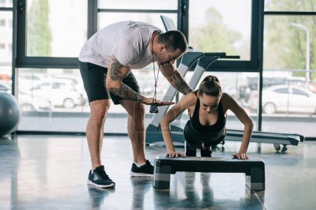 Photo for Male personal trainer helping sportswoman to do push ups at gym - Royalty Free Image