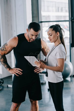 Photo for Female personal trainer and sportsman looking at screen of digital tablet at gym - Royalty Free Image