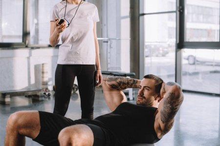 Photo pour Entraîneur personnel féminin utilisant minuterie tout sportif faisant abdos à la salle de gym - image libre de droit