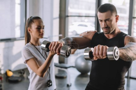 Photo for Female personal trainer helping sportsman to do exercises with dumbbells at gym - Royalty Free Image