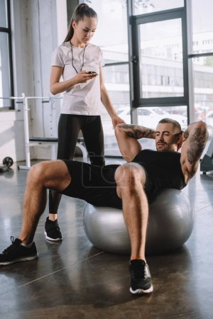 female personal trainer using timer while sportsman doing exercises on fitness ball at gym