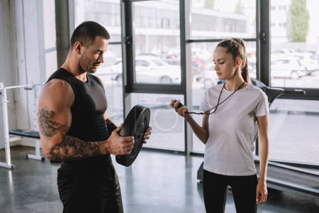 female personal trainer using timer while sportsman doing exercises with barbell disc at gym