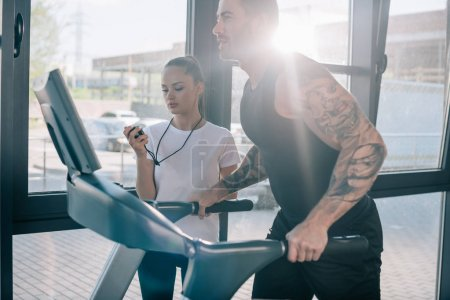 female personal trainer using timer and running sportsman at gym