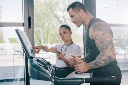 female personal trainer pointing at treadmill screen and running sportsman at gym