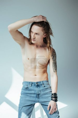 sexy shirtless man with long hair, on grey