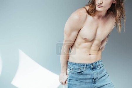 cropped view of young sexy shirtless man posing for fashion shoot, on grey