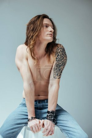 sexy tattooed shirtless man in jeans, isolated on grey