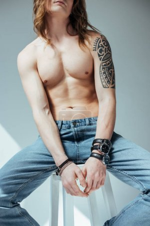 cropped view of sexy shirtless male model in jeans, on grey