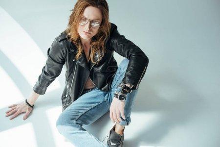 Photo pour Beau modèle masculin posant en lunettes, jeans et veste en cuir noir, sur gris - image libre de droit