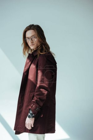 fashionable man with long hair posing in trench coat, on grey