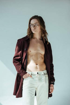 fashionable shirtless man in glasses posing in trench coat, on grey