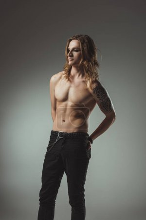 shirtless man with long hair and tattoo posing in black jeans, isolated on grey